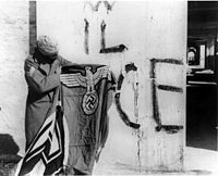 """A Sikh soldier of the 4th Division (the Red Eagles) of the Indian Army, attached to the British Fifth Army in Italy. Holding a captured swastika after the surrender of German forces in Italy, May 1945. Behind him, a fascist inscriptions says """"VIVA IL DUCE"""", """"Long live the Duce"""" (i.e. Mussolini)."""
