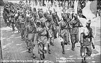 """French postcard depicting the arrival of 15th Sikh Regiment in France during World War I. The postcard reads, """"Gentlemen of India marching to chasten the German hooligans."""""""
