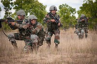 Indian Army soldiers move into position while demonstrating a platoon level ambush to U.S Army paratroopers.