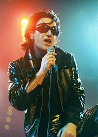 """Bono in March 1992 on the Zoo TV Tour portraying his persona """"The Fly"""", a leather-clad egomaniac meant to parody rock stardom."""