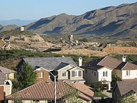 Newly constructed housing tract in the Alberhill Ranch neighborhood. Pacific Clay Products company mine in background.