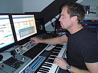 Music production in the 2000s using a digital audio workstation (DAW) with an electronic keyboard and a multi-monitor set-up.