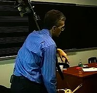 "Manhattan School of Music professor and professional double bass player Timothy Cobb teaching a bass lesson in the late 2000s. His bass has a low C extension with a metal ""machine"" with buttons for playing the pitches on the extension."