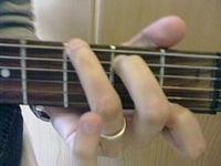 When musicians play three or more different notes at the same time, this creates a chord. In Western music, including classical music, pop music, rock music and many related styles, the most common chords are triads– three notes usually played at the same time. The most commonly used chords are the major chord and the minor chord. An example of a major chord is the three pitches C, E and G. An example of a minor chord is the three pitches A, C and E. (Pictured is a guitar player performing a chord on a guitar).