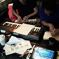 People composing music in 2013 using electronic keyboards and computers.