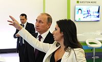 """President Putin with Margarita Simonyan in front of RT's """"Question more"""" slogan (2015)"""
