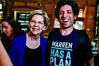 """Warren with a supporter wearing a """"Warren has a plan for that"""" T-shirt. The phrase became an internet meme during her presidential run."""