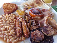The full breakfast is among the best known British dishes, consisting of fried egg, sausage, bacon, mushrooms, baked beans, toast, fried tomatoes, and sometimes white or black pudding