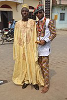 Cameroonian fashion is varied and often mixes modern and traditional elements. Note the wearing of sun glasses, Monk shoes, sandals, and a Smartwatch.