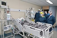 A critically ill patient receiving invasive ventilation in the intensive care unit of the Heart Institute, University of São Paulo. Due to a shortage of mechanical ventilators, a bridge ventilator is being used to automatically actuate a bag valve mask.