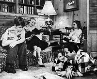 The Comos at home c. 1955. On the sofa are his older son Ronnie and wife Roselle. In the chair with her doll is his daughter, Terri, and reading on the floor are son David and his Dad.