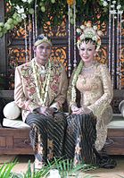 A Javanese couple wearing their traditional garbs during marriage.