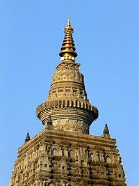 The stupa finial on top of the pyramidal structure.
