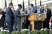 Cruz presents a U.S. flag to World War II veteran Richard Arvin Overton during opening ceremony for outpatient clinic in Austin on August 22, 2013