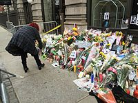 A woman places flowers outside Bowie's apartment in New York on Lafayette Street the day after his death was announced.