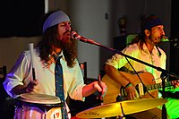"""David """"Hoag"""" Kepner (left) sings as the lead vocalist while playing the drums during a performance in the Drop Zone at Cannon Air Force Base, New Mexico, while a rhythm guitarist sings backup vocals."""