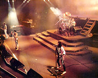 Queen performs in a typical rock band layout during a 1984 concert. Lead singer (front man) Freddie Mercury stands centre-stage in front of drummer Roger Taylor and positioned between bass guitarist John Deacon and lead guitarist Brian May.