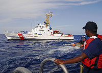 A boatswain's mate keeps watch on a small boat it heads for the USCGC Chandeleur in 2008