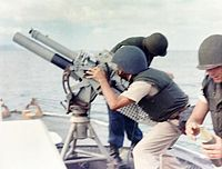 A gun crew on board firing an 81mm mortar during the bombardment of a suspected Viet Cong staging area one mile behind An Thoi in August 1965