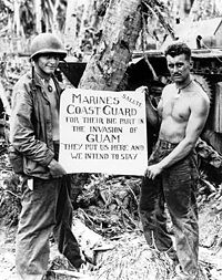 Marine Corps Privates First Class William A. McCoy and Ralph L. Plunkett holding a sign thanking the Coast Guard after the Battle of Guam in 1944