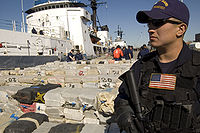 A Coast Guardsman stands guard over more than 40,000 pounds of cocaine worth an estimated $500 million being offloaded from the Cutter Sherman, 23 April 2007. The drugs were seized in three separate busts near Central America. The offload included approximately 38,000 pounds of cocaine seized in the largest cocaine bust in maritime history.