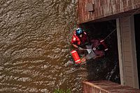 A Coast Guard Aviation Survival Technician assisting with the rescue of a pregnant woman during Hurricane Katrina in 2005