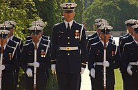 The United States Coast Guard Ceremonial Honor Guard wears Full Dress Blue with white gun belts at the Tomb of Unknown Soldiers.
