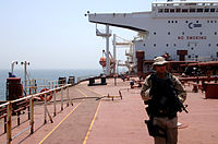 A member of USCG Law Enforcement Detachment (LEDET) 106 performing a security sweep aboard a tanker ship in the North Persian Gulf in July 2007