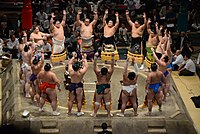 Sumo wrestlers form around the referee during the ring-entering ceremony