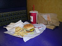 A meal including small French fries, a Whopper Jr., a drink, and packets of Heinz ketchup.