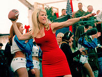 Brinkley winds up to throw an autographed football into the audience during a USO show in the Eagle Sports Complex at Tuzla Air Base, Bosnia and Herzegovina (December 22, 1999)