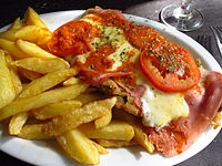 """""""Milanesa a la napolitana"""" with French fries, an Italian-inspired dish based on the original cotoletta dish from Milan, common in South America. This dish is called """"parmegiana steak"""" in Brazil, though it is not typical from Parma region in Italy but was actually invented in Buenos Aires."""