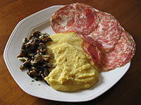 Polenta served with sopressa and mushrooms, a traditional peasant food of Veneto