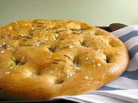 Focaccia with rosemary. Focaccia is widely associated with Ligurian cuisine
