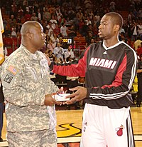 Wade giving a present to a U.S. Army reservist during a 2009 pregame ceremony