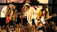 Brad Whitford, Steven Tyler, and Joe Perry of Aerosmith performing at the NFL Kickoff in Washington, D.C., on September 4, 2003
