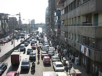 People walk, drive and cycle through a street in Cairo.
