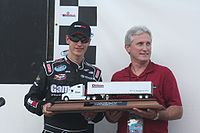Logano holds his trophy for winning the pole position in Nashville