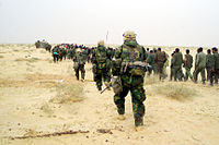 US Marines escort captured enemy prisoners to a holding area in the desert of Iraq on 21 March 2003.