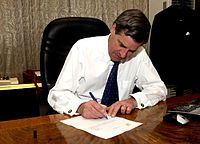 Coalition Provisional Authority director L. Paul Bremer signs over sovereignty to the appointed Iraqi Interim Government, 28 June 2004.