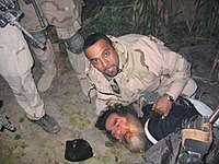 Saddam Hussein being pulled from his hideaway in Operation Red Dawn, 13 December 2003