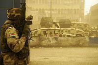 An Iraqi soldier and vehicles from the 42nd Brigade, 11th Iraqi Army Division during a firefight with armed militiamen in the Sadr City district of Baghdad 17 April 2008