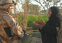 A woman pleads with an Iraqi army soldier from 2nd Company, 5th Brigade, 2nd Iraqi Army Division to let a suspected insurgent free during a raid near Tafaria, Iraq.