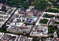 Aerial view of Albertopolis. Albert Memorial, Royal Albert Hall and Royal College of Art are visible near the top; Victoria and Albert Museum and Natural History Museum at the lower end; Imperial College, Royal College of Music, and Science Museum lying in between.
