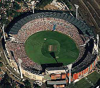 In 1992 the West Coast Eagles became the first non-Victorian team to win an AFL premiership. Pictured is the Melbourne Cricket Ground in 1992 where the grand final was held. The stadium is pictured as configured for a cricket match, note the visible pitch and absent goal posts.