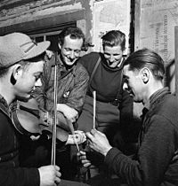 French-Canadian lumberjacks playing the fiddle, with sticks for percussion, in a lumber camp in 1943.