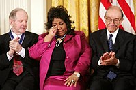 Franklin wipes a tear after being given the Presidential Medal of Freedom on November 9, 2005, at the White House. She is seated between fellow recipients Robert Conquest (left) and Alan Greenspan