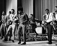Brown (middle) and The Famous Flames (far left to right, Bobby Bennett, Lloyd Stallworth, and Bobby Byrd), performing live at the Apollo Theater in New York City, 1964