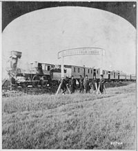 Directors of the Union Pacific Railroad gather on the 100th meridian, which later became Cozad, Nebraska, about 250 mi west of Omaha in the Nebraska Territory, in October 1866. The train in the background awaits the party of Eastern capitalists, newspapermen, and other prominent figures invited by the railroad executives.