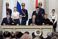 Vladimir Putin (third, left), Sergey Aksyonov (first, left), Vladimir Konstantinov (second, left) and Aleksei Chalyi (right) sign the Treaty on Accession of the Republic of Crimea to Russia in 2014